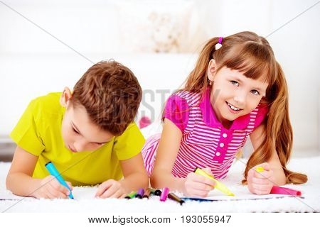 Two happy kids spending time at home, drawing. Free time, activity and hobby. Education. Family at home.