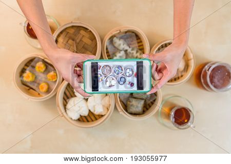 Top view of cellphone taking photo on dim sum