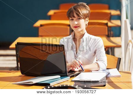 Young fashion business woman using laptop at sidewalk cafe. Stylish female model in white blouse outdoor