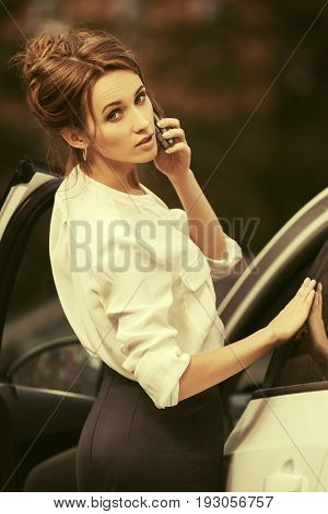Young fashion business woman talking on mobile phone beside a car. Stylish female model in white blouse outdoor