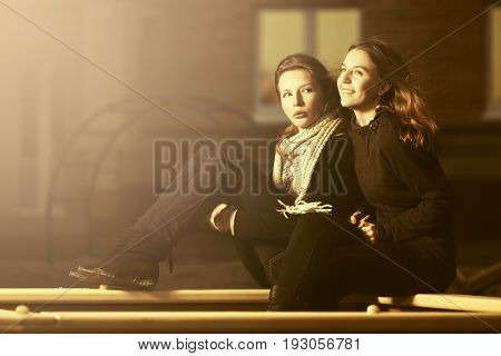 Two happy fashion teen girls on the playground
