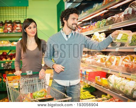 People taking vegetables in a supermarket