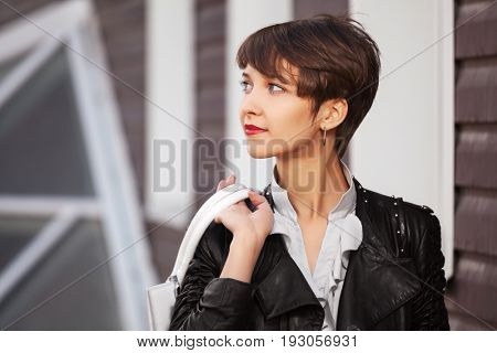 Happy young fashion woman with handbag walking in city street. Stylish female model in black leather jacket outdoor