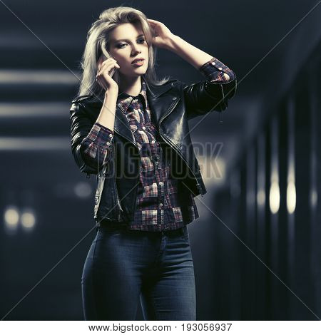 Young fashion blond woman talking on mobile phone in a subway. Stylish female model in black leather jacket and blue jeans