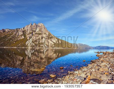 Picturesque mountain in Bariloche, Argentina. The concept of exotic and extreme tourism. The summer sun illuminates the picturesque landscape