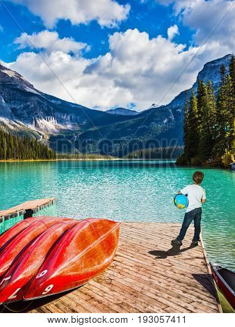 Emerald Lake in Yoho Park in the Canadian Rockies. The seven-year slender boy with the globe in hands admire nature