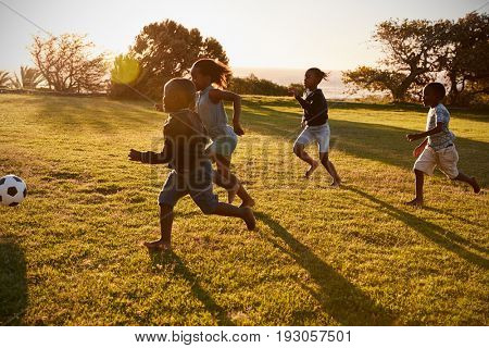 Four elementary school kids playing football in a field