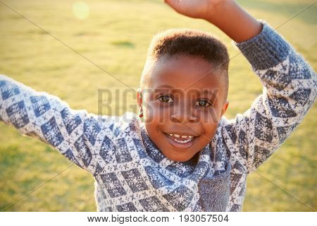 African elementary school boy waving to camera outdoors