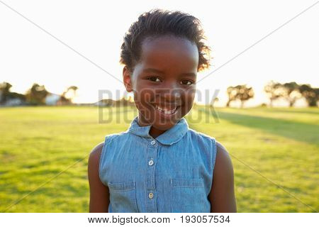 African elementary school girl smiling in a park, close up