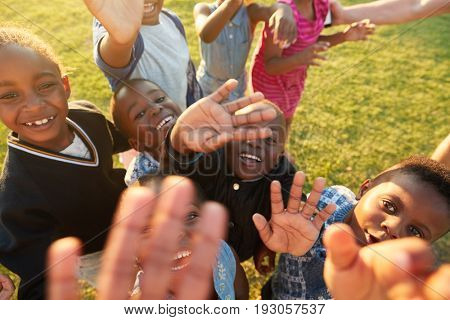 Elementary school kids in a field look up at  camera waving