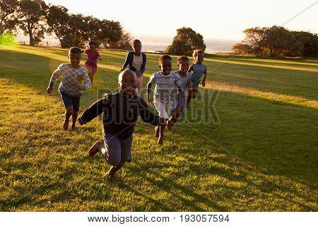 African elementary school kids running to camera in a field