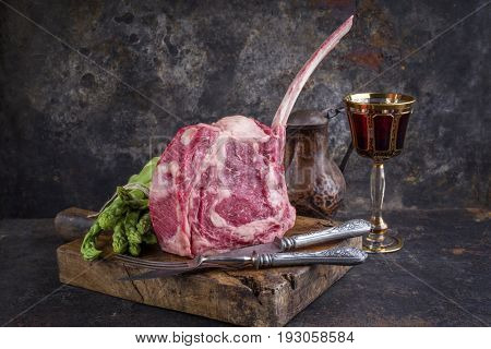 Raw dry aged Wagyu Tomahawk Steak with green asparagus as close-up on old cutting board