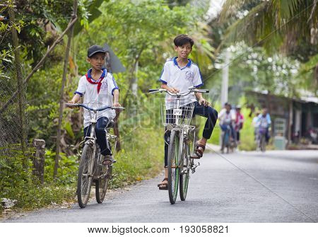 An Binh Island, Vietnam - March 25, 2017 : Vietnamese pioneers go home from school by bicycles on An Binh island, Vinh Long, Vietnam