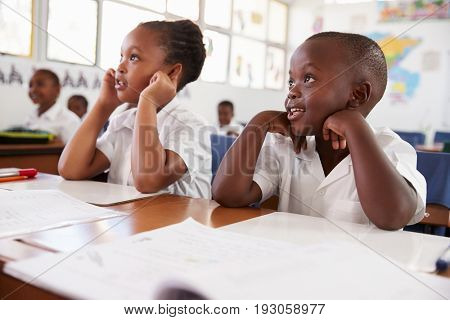 Two kids listening during a lesson at an elementary school