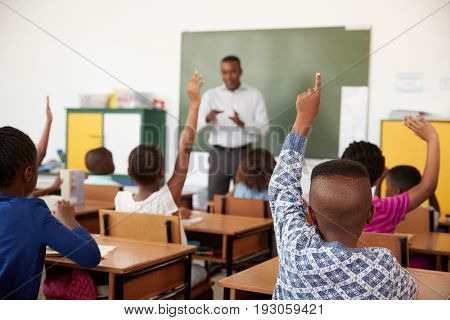 Kids raising hands during a lesson at an elementary school