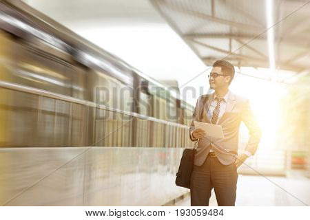 Asian businessman using digital tablet pc at commuter platform, with beautiful sun flare at background.