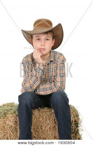 Cowboy Sitting On Hay Bale