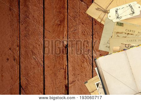 Grunge background with retro book and vintage postcards on old wooden planks. Inscription on the card - carte postale - postcard in french. Copy space for text