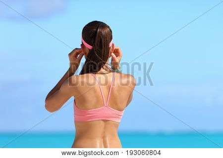 Runner girl putting on in-ear headphones getting ready for run on beach listening to music with earphones wearing wearable tech accessories.