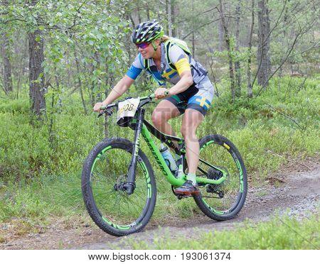 STOCKHOLM SWEDEN - JUNE 11 2017: Smiling female mountain bike cyclist at Lida Loop Mountain bike Race. June 11 2017 in Stockholm Sweden