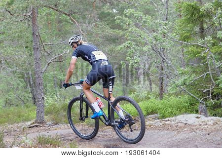 STOCKHOLM SWEDEN - JUNE 11 2017: Side rear view of female mountain bike cyclist in the forest on a rock at Lida Loop Mountain bike Race. June 11 2017 in Stockholm Sweden