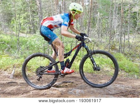 STOCKHOLM SWEDEN - JUNE 11 2017: Side view of female mountain bike cyclist in the forest at Lida Loop Mountain bike Race. June 11 2017 in Stockholm Sweden