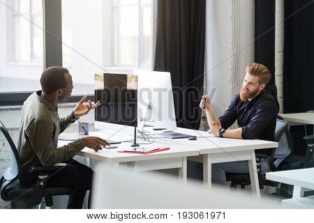 Two young male colleagues sitting at opposing desks and discussing new business project at the office