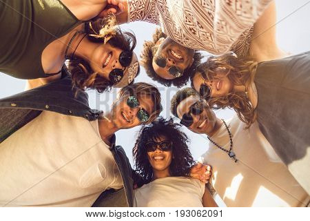 Multiethnic group of friends huddle join in a circle and looking down outdoors