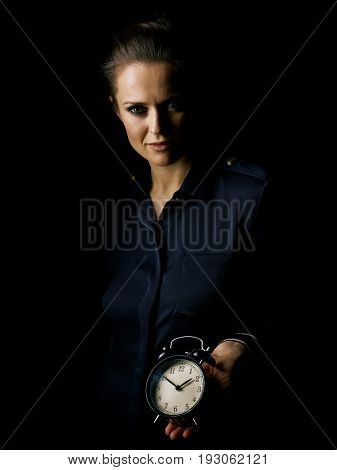 Coming out into the light. Portrait of woman in the dark dress isolated on black showing alarm clock