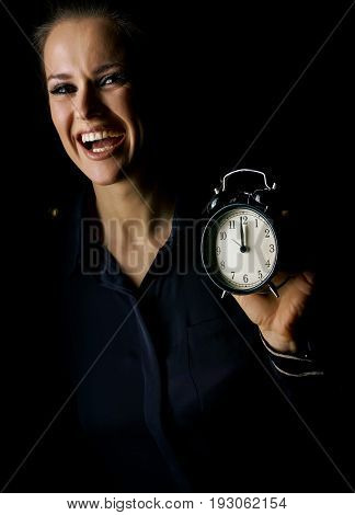 Coming out into the light. smiling woman in the dark dress isolated on black showing alarm clock