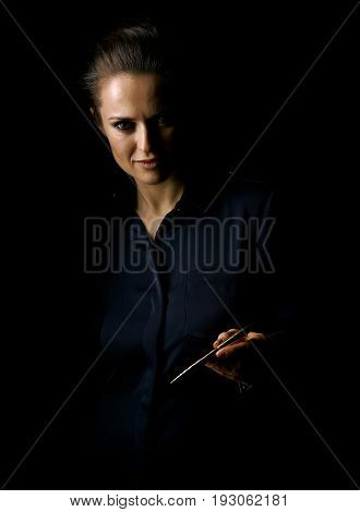 Coming out into the light. Portrait of woman in the dark dress isolated on black giving a pen