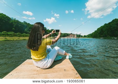 womam sitting on a lake pier in sunny day and taking picture