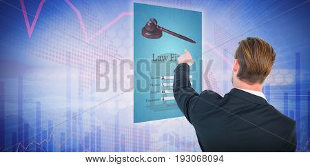 Rear view of young businessman in suit pointing against stocks and shares