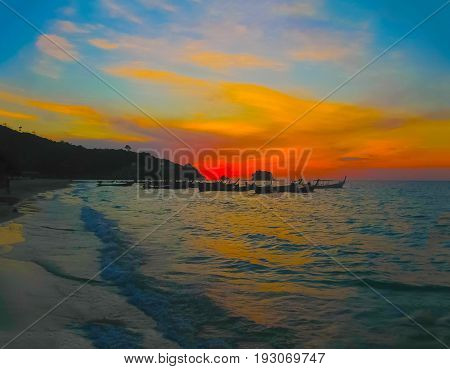 Small boats at the Andaman Sea in sunset. Nai Yang beach