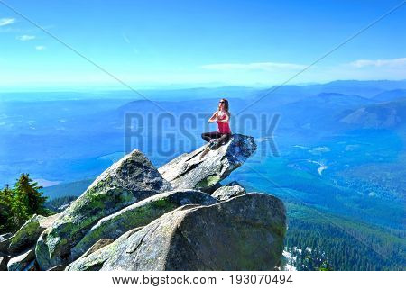 Meditation on rock with mountains and valley views. Mount Pilchuck. Cascade Mountains.  Seattle. Washington. United States.