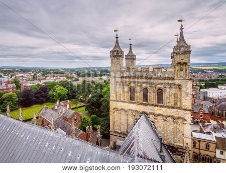 View of the city of Exeter from one of the towers of the cathedral. Also one of the towers is visible in the foreground. Devon. England