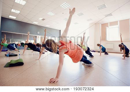 Close-up of a group of girls team engaged in fitness and stretching muscles in the gym. Concept friends are involved in sports.