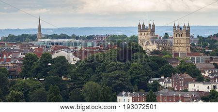 Panoramic view of the city of Exeter. The cathedral and the church of St Michael are well seen. Many large trees and small houses. City center. Devon. England