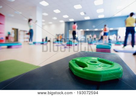sports wheel weighting agent for the bars lies on the stand for a step against the background of a group of girls engaged in fitness and crossfit. Concept sports equipment.