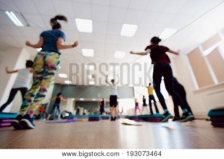 Blurred background of people group of girls playing in yoga and fitness,crossfit in the gym.