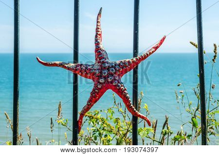 Metal Ornament On A Balustrade In A Coastal Town, A Symbolic Starfish Shaped Element