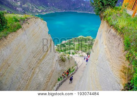 QUITO, ECUADOR - NOVEMBER, 25 2016: Unidentified people walking in a path to enjoy the beautiful and amazing view of lake with a beautiful magenta color of the Quilotoa caldera, . Quilotoa is the western volcano in Andes range and is located in andean reg