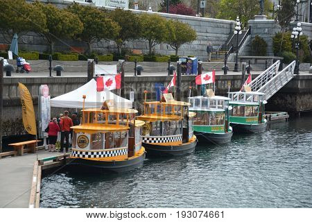 Victoria BC,Canada,April 21st 2015.Water taxis lined up in Victoria's inner harbor waiting to take tourists on an adventure.