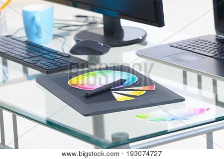 Designer workplace, computers. color wheel and swatches of colour with stylus on a graphic tablet