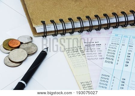 saving account passbooks and coins with pen and notebook for financial planning concept