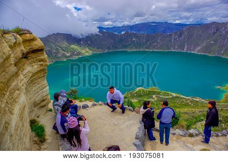 QUITO, ECUADOR - NOVEMBER, 25 2016: Unidentified people taking pictures and enjoying the view of lake with a beautiful magenta color of the Quilotoa caldera. Quilotoa is the western volcano in Andes range and is located in andean region of Ecuador.