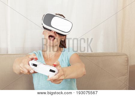 Beautiful young women wth VR headset and joystick playing virtual reality in living room.