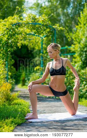 Young fitness woman doing fitness exercises in the park on green grass. Fitness training outdoors. Fitness classes outdoors. Attractive fitness woman. Workout outdoors. Healthy lifestyle