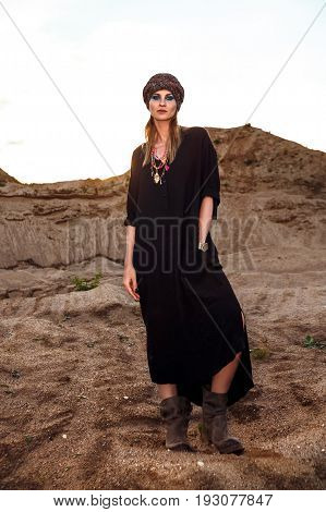 fashion portrait of female in black clothes standing among sand hills