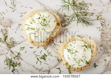 Sesame bagel with cream cheese dill and salt on table